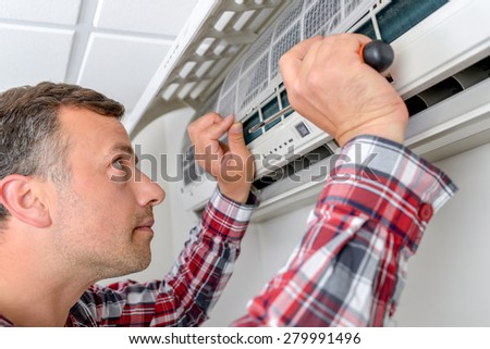 Repairing an air conditioning unit - stock photo