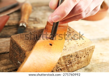 Repairing leather belt in workshop - stock photo