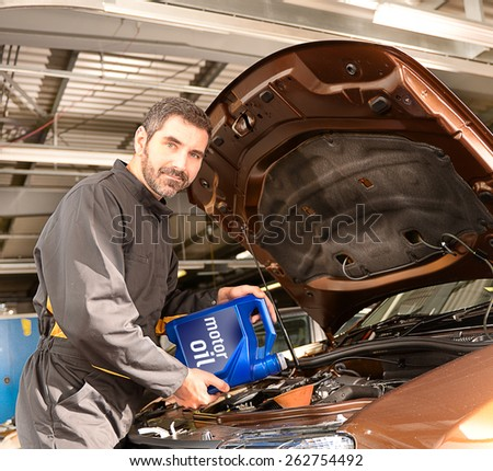Repairman auto mechanic inspecting and refilling engine with motor oil during automobile maintenance at engine auto repair shop service station - stock photo