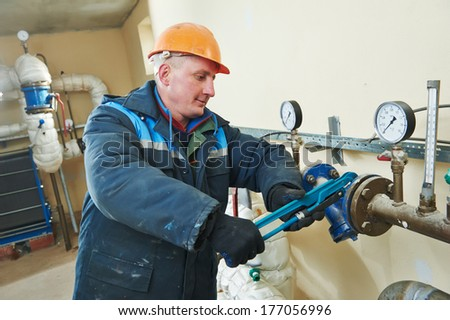 repairman engineer of fire engineering system or heating system open the valve equipment in a boiler house - stock photo