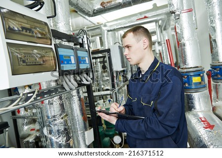 repairman engineer or inspector of fire engineering system or heating system with valve equipment in a boiler house - stock photo