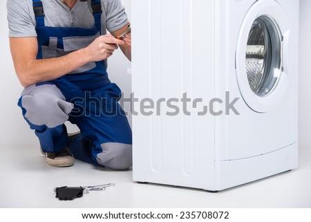 Repairman is repairing a washing machine on the white background. - stock photo