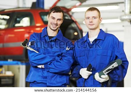 repairman mechanic workers at car engine auto repair shop service station - stock photo