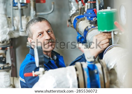 repairman plumber engineer of fire engineering system or heating system open the valve equipment in a boiler house - stock photo