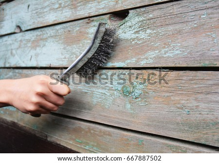 repairman remove the old paint from the wooden surface with wire brush