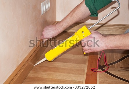 Repairman's hands Installing Skirting Board Oak Wooden Floor with Caulking Gun Silicone from Cartridge. Flooring with Wooden Batten Repair. - stock photo
