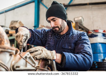 repairman worker repairing a engine excavator - stock photo