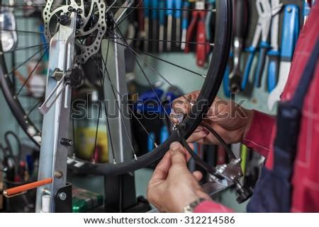 Repairs bicycle. - stock photo