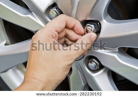 Replacing lug nuts by hand while changing tires on a vehicle. - stock photo