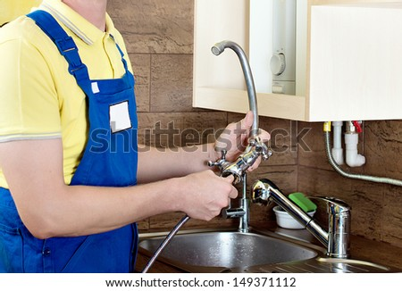 Replacing the faucet in the kitchen. Plumbing works at home. Smiling handsome plumber with an adjustable wrench - stock photo
