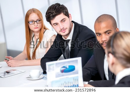 Report on the work. Confident businessman sitting at the table at a business meeting in the office and keep the documents in his hand while businessman looking at chief