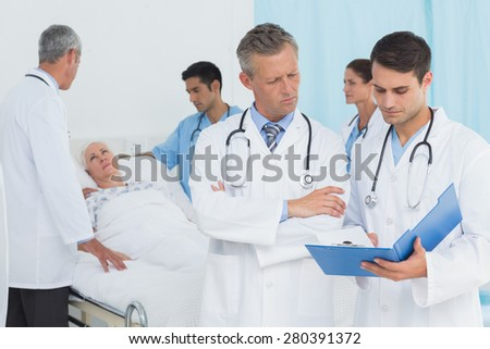Report reading with colleagues and patient behind at hospital - stock photo