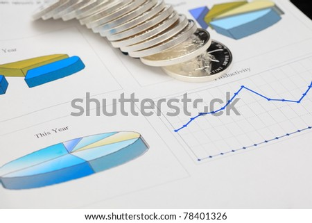 report with diagrams and silver coins on it - stock photo