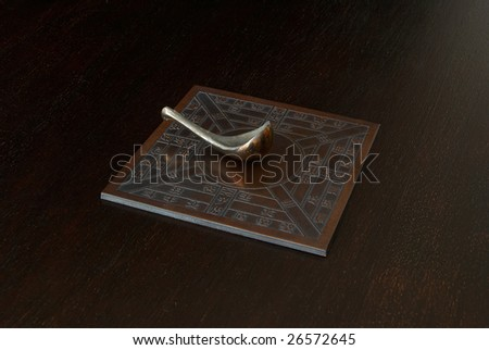 Reproduction of an ancient Chinese compass (which points south) on a dark wooden bench - stock photo
