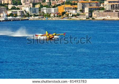 rescue aircraft landing on the sea to put water in. operation to extinguish a forest fire. - stock photo