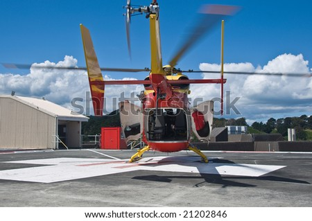 Rescue Helicopter Waiting on Hospital Rooftop Pad - stock photo
