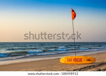 Rescue surfboard on the sand beach near the sea or ocean - stock photo