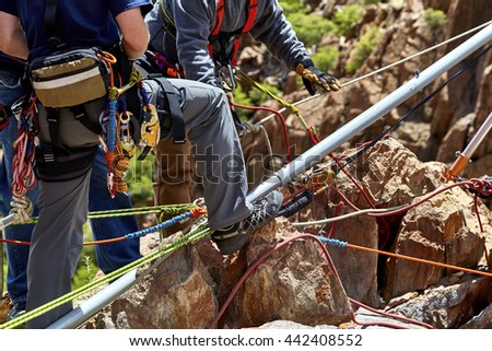 Rescue Workers on mountain ledge setting up a vortex multipod for a practice rescue drill - stock photo