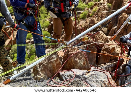 Rescue workers on mountain ledge setting up vortex multipod with ropes - stock photo