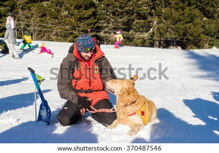 Rescuer and his service dog at Mountain Rescue Service at Bulgarian Red Cross are cheering after successfully rescuing a avalanche victim in a training, Vitosha mountains, Bulgaria, January 28, 2016. - stock photo