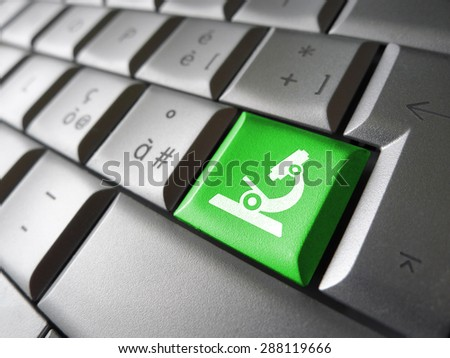 Research concept with microscope icon and symbol on a green laptop computer key for medical and online business.