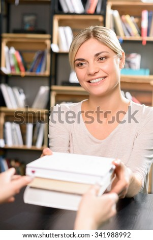 Research finished. Young beautiful woman is smiling while returning all books to the library.  - stock photo