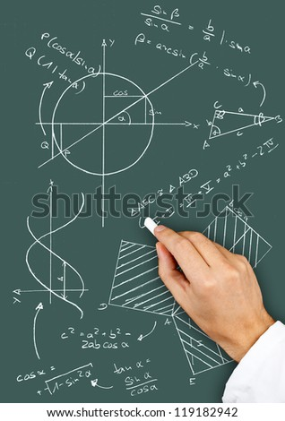 Research scientist writing maths diagrams and formulas with chalk on blackboard - stock photo
