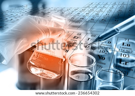 researcher dropping the reagent into test tubes with periodic table background. - stock photo