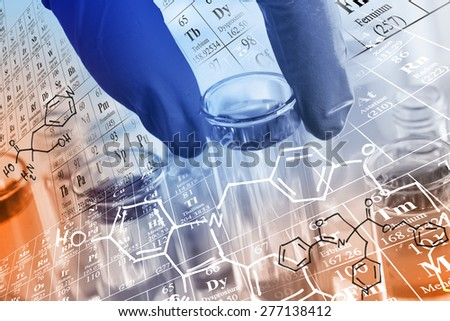 Researcher 's gloved hand holding the test tubes at laboratory, with chemical equations and periodic table background. - stock photo