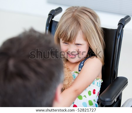 Reserved little girl sitting on the wheelchair at the hospital - stock photo