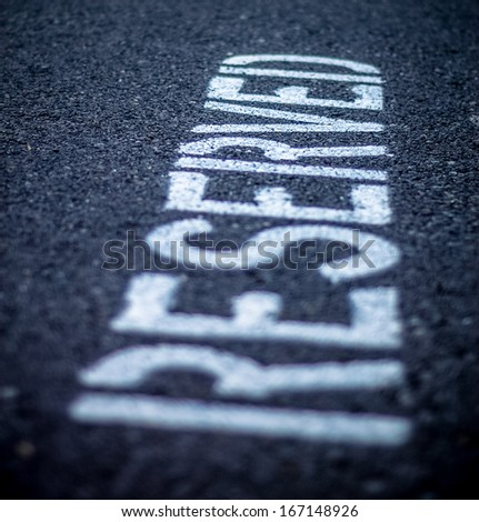 Reserved Sign Painted On Asphalt Road Parking Place - stock photo