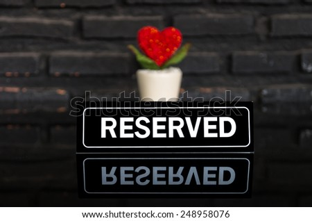 reserved signboard with heart on the table - stock photo