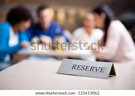 reserved table at nice restaurant with guests in the background - stock photo