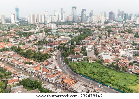 Residential area right in the center of Jakarta, the capital city of Indonesia. The city is still composed of lots of villages in the center which contrast sharply with the modern buildings. - stock photo