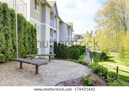 Residential backyard with wooden benches and trimmed hedges overlooking park