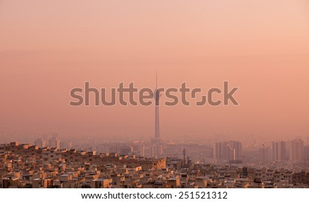 Residential buildings in front of Milad Tower in air-polluted skyline of Tehran at pink sunset. - stock photo