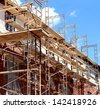 Residential construction in the process of being built as a real estate structure with metal scaffolding as a business symbol of economic investment rise with financial growth in a healthy economy. - stock photo