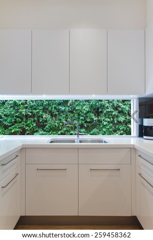 Residential contemporary kitchen sink with low window showing a green hedge - stock photo