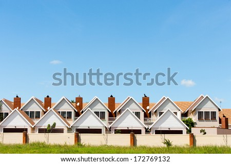 Residential fenced house complex against blue sky. - stock photo