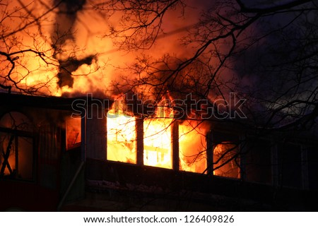 residential home on fire, fully involved, engulfed in orange fire and flames - stock photo