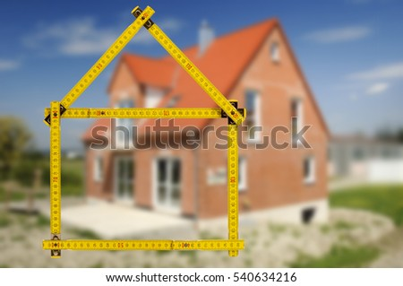 residential house in construction for sale seen through an folding rule