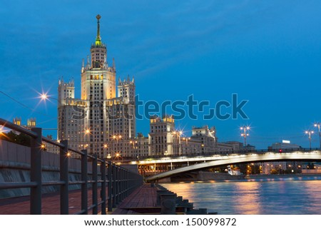 Residential house on Kotelnicheskaya Embankment and the bridge across the Moscow river in the evening - stock photo