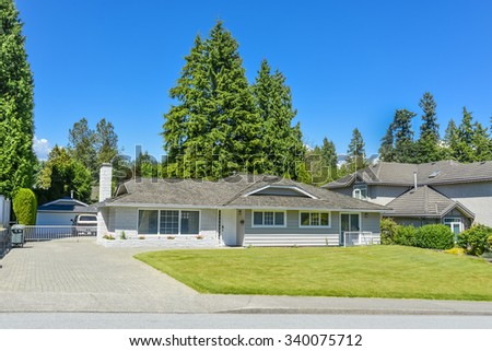 Residential house on sunny day with landscaped lawn in front and blue sky background. Suburban house with concrete driveway and asphalt road in front. - stock photo