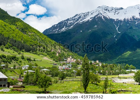 Residential houses and ancient towers in Mestia with snow-capped mountains in the background