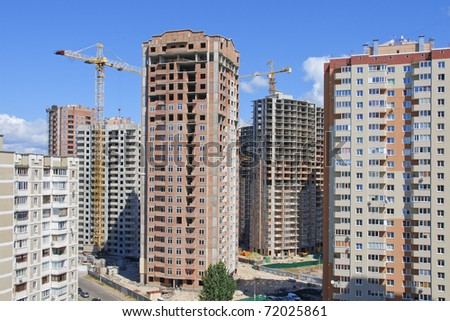 Residential houses under construction in a new city district - stock photo