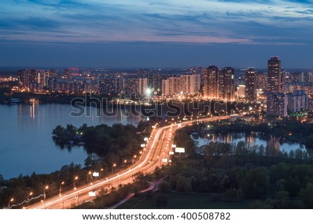 Residential illuminated district, highway, lake at summer night in Moscow, Russia