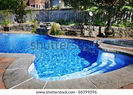 Residential inground swimming pool in backyard with waterfall and hot tub - stock photo