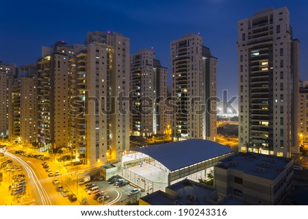 Residential street with new tall buildings at night - stock photo