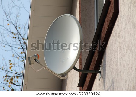 Residential TV receiver satellite dish mounted on a modern cottage
