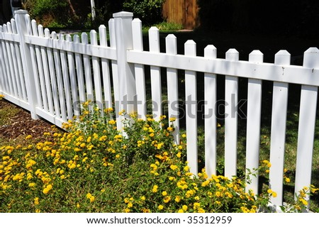 Residential white picket fence with yellow flower accents - stock photo